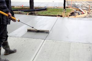Concrete Preparation by worker with a broom